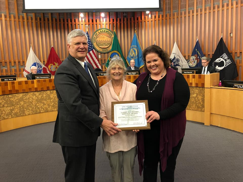 Mayor Don Anderson and Sally Saunders present the award to Gayle Selden at Lakewood City Hall.